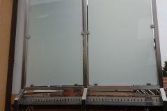 Windfang mit VSG Glas mit matter Folie - Rahmen aus Edelstahlrohr, geschliffen Korn 240
