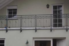 Geländer mit Kreuzen und Blumenkastenhaltern