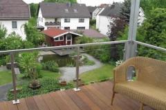 Geländer mit Glasfüllung - feuerverzinkt - Pfosten auf Holzboden gesetzt -der Blick in den Garten bleibt ungetrübt
